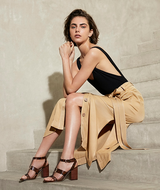 Woman sitting on steps wearing Marc Fisher Summer 19 sandals.