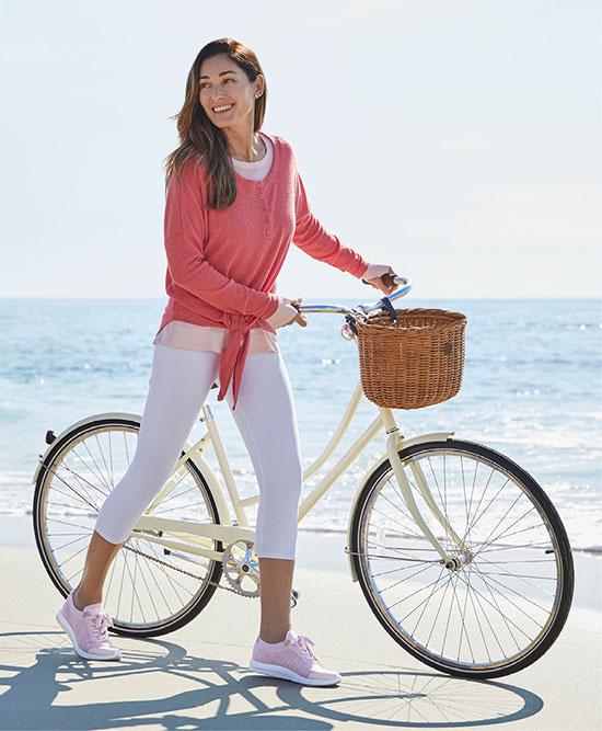Woman riding a bike on a beach.