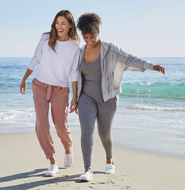 Two women walking on a beach.