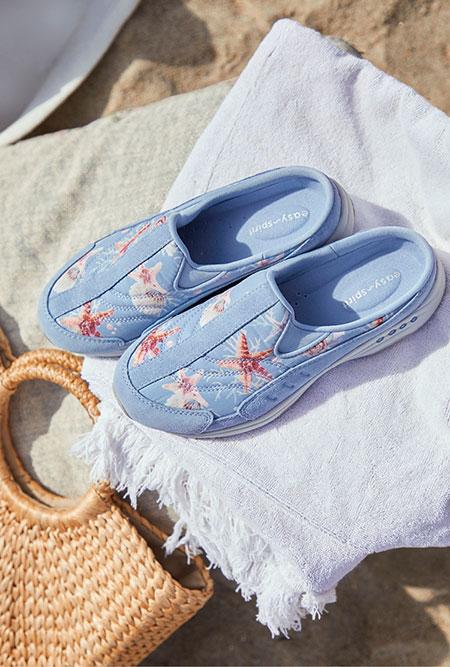 Pair of Easy Spirit sandals on beach.