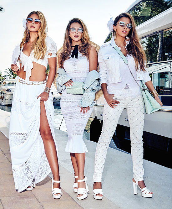 3 women standing next to a boat wearing all white and Guess heels.