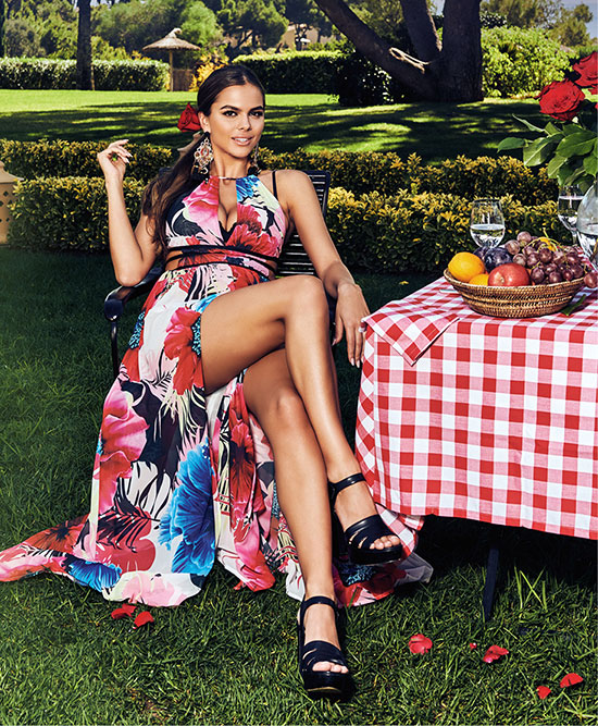 A woman sitting in a floral dress at a picnic wearing Guess heels.