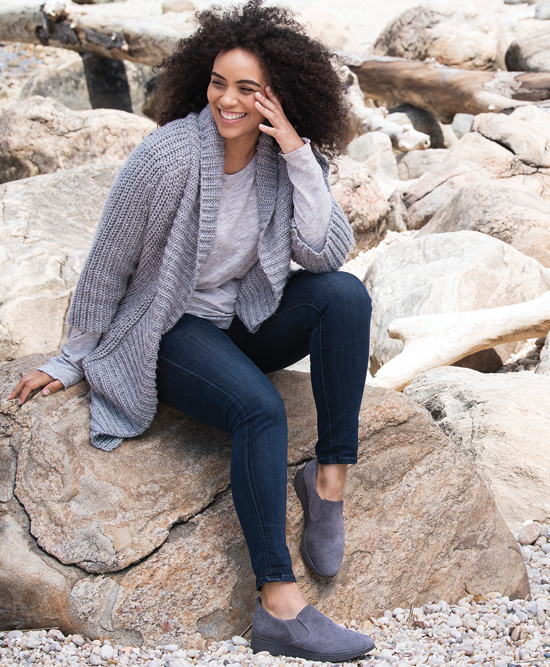 Woman sitting on beach wearing Easy Spirit.