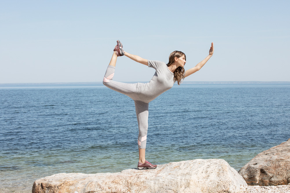 Woman posing on beach wearing Easy Spirit.
