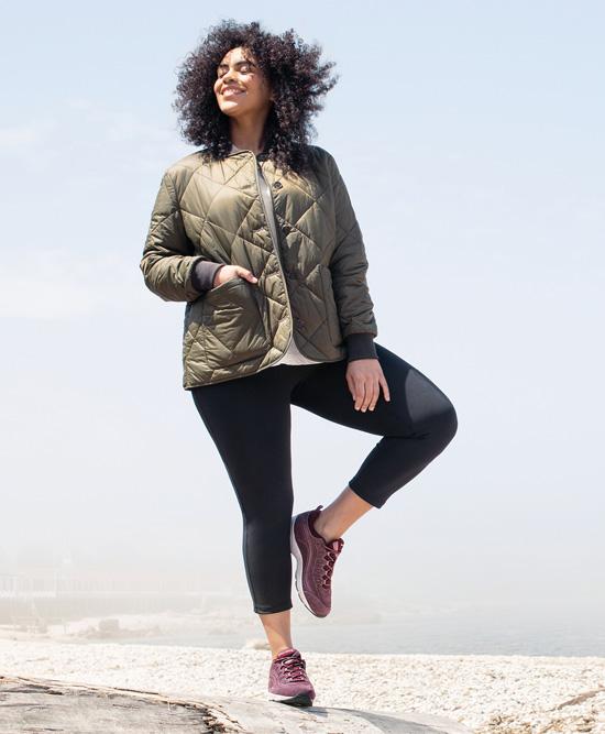 Woman standing on beach in Easy Spirit sneakers.
