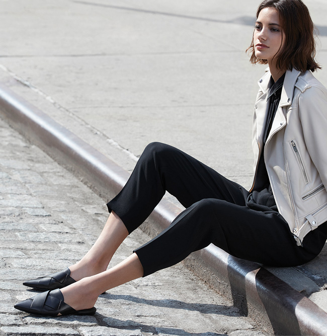 Woman sitting on city street burb wearing Sigerson Morrison black sandals.