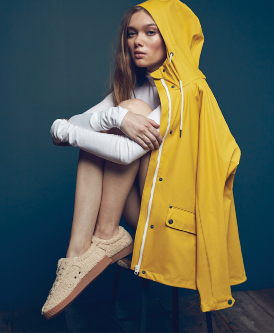 Woman sitting on chair with yellow rain coat draped over her hear, wearing Tretorn shoes.