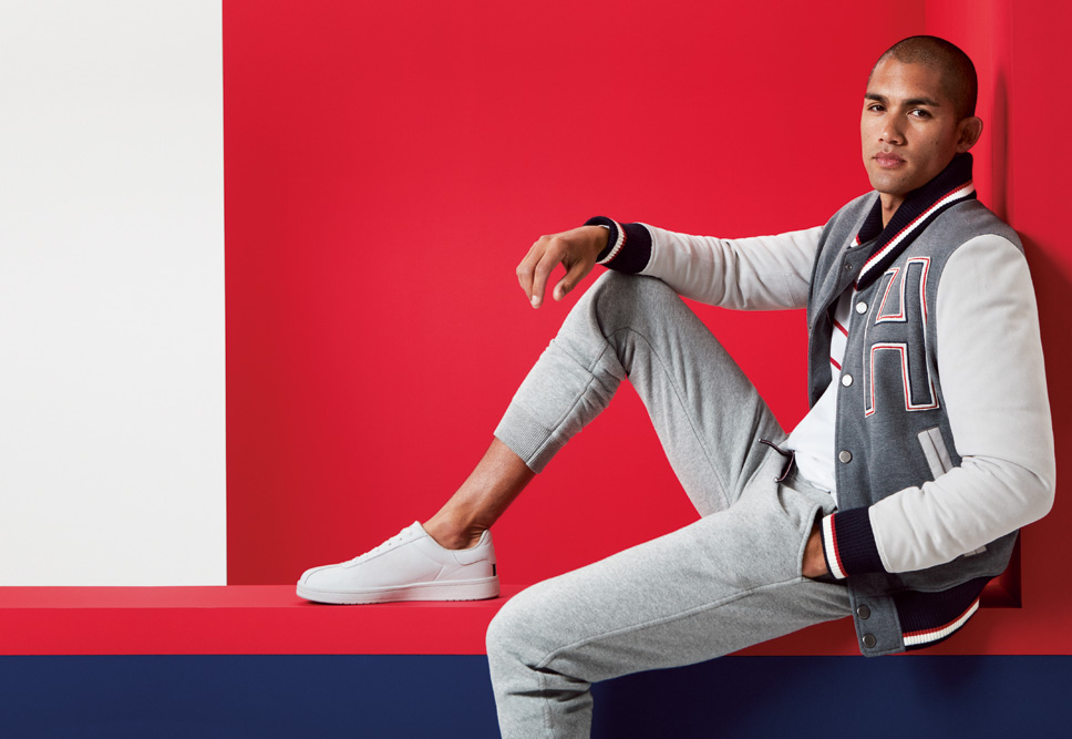 Man sitting with one leg up in a scholastic-style Tommy Hilfiger jacket and sneakers.