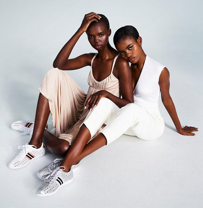 Two women sitting wearing sporty Nine West sneakers.