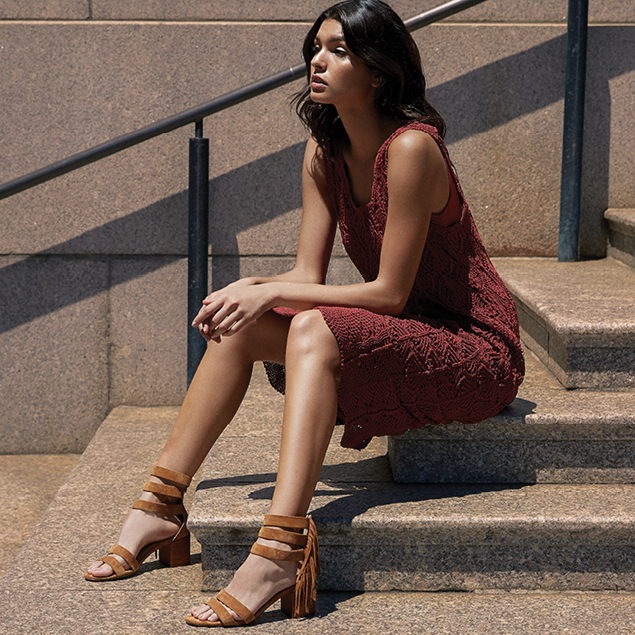 Woman sitting on steps in a sun dress and tassel sandals, representing the Sigerson Morrison brand.