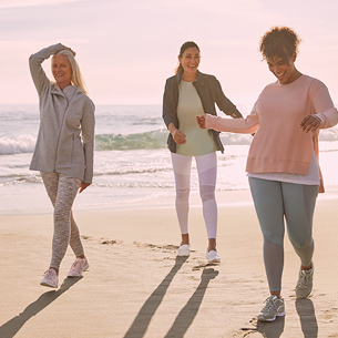 Three women walking on a beach, representing the Easy Spirit brand.