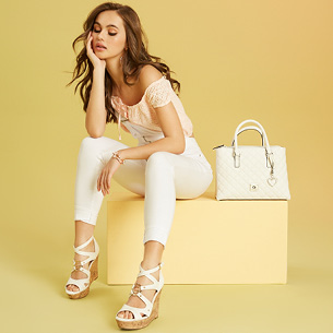 Girl sitting with black high heeled sandals on, representing G by Guess.