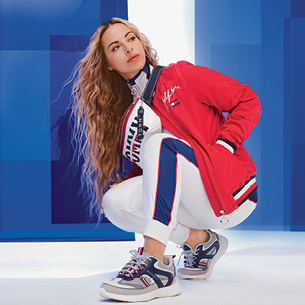 Woman standing in a red, white and blue outfit, representing Tommy Hilfiger