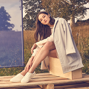 Girl siting on wood planked floor in socks and sneakers representing the Tretorn brand.